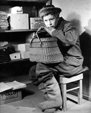 Maalaispoika Nieminen (Lasse Pöysti) istuu kellarissa kori sylissä.