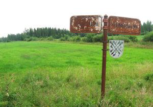 Vehmersalmen ja Tuusniemen vanhan rajan ruostunut kyltti.