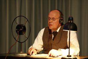 Hannu-Pekka Björkman radion alkuaikojen kuuluttajana Sinun tarinasi – Yle 90 -juhlalähetyksessä.