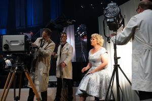 Maria Sid ja Yleisradion insinööreiksi pukeutuneita miehiä Yle 90 -juhlalähetyksessä