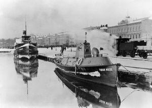 Kauppatorin rantaa. Linnanlaituri ja juna Satamaradalla. Rannassa 1915 valmistunut yhteysalus ja myöhemmin linnoitusmiinavene /-raivaaja Fabian Wrede.