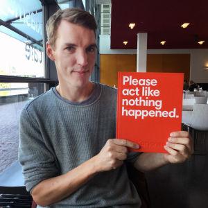 Otto Karvonen pitää kädessä uutta kirjaansa.