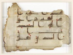 Detail of page showing fragment of Qur'an text. Written in blackish brown ink on vellum, these fragments of the Qur'an have a variety of origins and chart the change from the angular Kufic to more cursive Naskhi variation of the Arabic alphabet. Although