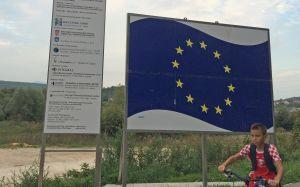 Två skyltar, den ena med EU:s flagga på, i förgrunden en pojke på cykel. Taget i Kroatien.