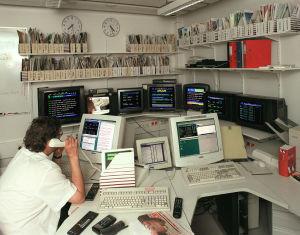 Toimittaja, työpöytä ja monitoreja Teksti-tv:n urheilutoimituksen työhuoneessa