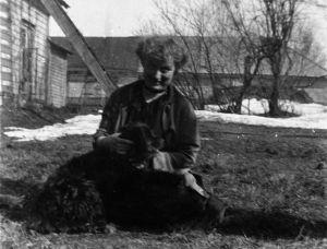 Edith Södergran istuu pihassa koira sylissään
