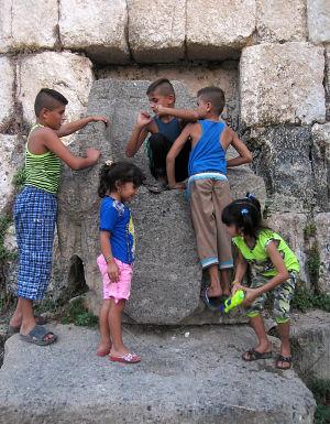 lapset leikkivät foinikialaisen temppelin raunioilla Sidonissa