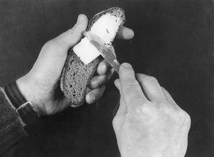 Leipä ja voi (rasva, margariini). Miehen kädet voitelevat leipäpalaa veitsellä.  Voileipä, ruisleipä. Siivu limpusta. Rasvan käyttö. Veitsi.