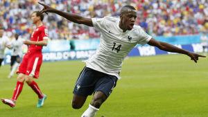 Ranskan Blaise Matuidi tuulettaa maalia, taustalla Sveitsin pelaaja ja yleisöä.