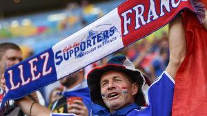 Ranskan joukkueen kannattaja pitää päänsä yläpuolella fanihuivia.