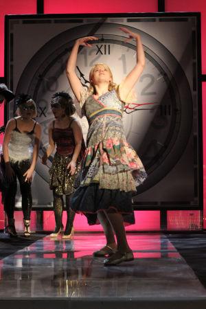 Vilma lavalla, kädet ylhäällä kellotaulun edessä. Taustalla tanssijoita, taustan väri punainen.