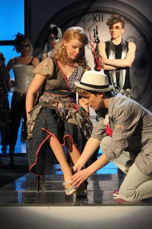 Jani sovittaa kenkää Vilman jalkaan. Taustalla tanssijat katsovat.