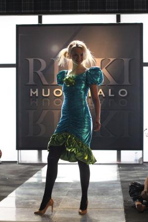 Tanssija hienossa sinivihreässä mekossa Rikki muotitalon kyltin edessä.