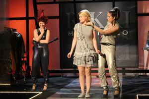 Emmi, Vilma ja Krista lavalla. Tausta punainen.
