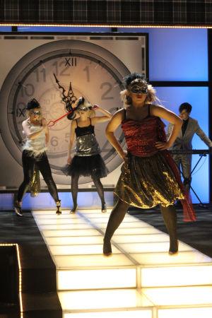 Tanssijoita lavalla kellotaulun edessä, naamiot silmillään.