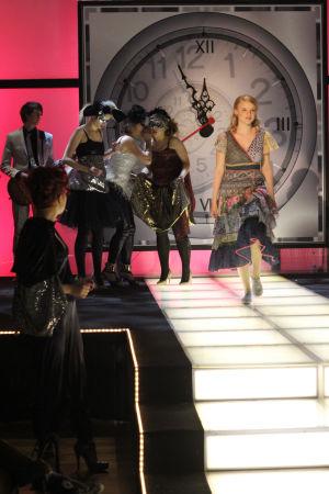 Vilma lavalla pitkä mekko päällään. Taustalla tanssijoita. Emmi seisoo lavan edessä.