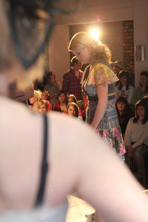 Vilma. Edessä tytön olkapää ja taustalla yleisöä.