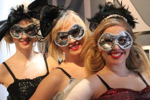 Kolme tanssijaa hatut päässään ja naamiot kasvoillaan.