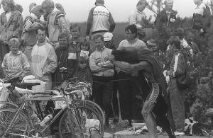 Triathlonkilpailija vaihtaa uimapukua pyöräilyasuun katsojien edessä.