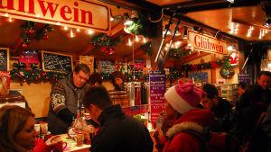 Ihmisiä glögikojun edessä saksalaisella joulutorilla.