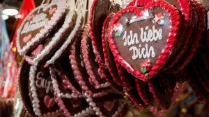Sokerikuorrutuksella koristeluja isoja sydänpipareita, joissa lukee Ich liebe Dich (minä rakastan sinua), roikkuu nipuissa.