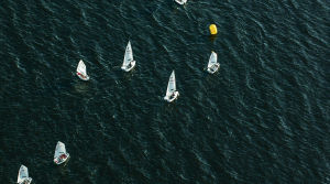 Flybild över havslandskap och jollesegling.