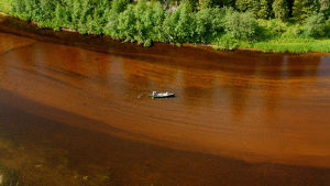 Flygbild över somrigt Finland och grunt vattendrag.