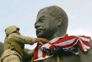 Amerikansk soldat virar en amerikansk flagga runt staty av Saddam Hussein