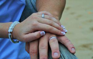 Kvinnas hand på en mans hand, med ringar
