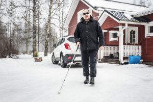 Markku Tallila valkoisen kepin kanssa kotipihallaan.