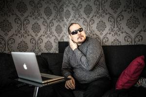 Markku Tallila istuu olohuoneen sohvalla tietokone edessään.