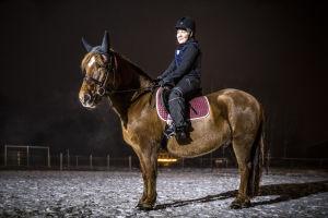 Salla Huhtala istuu Väiski-hevosen selässä aitauksessa.