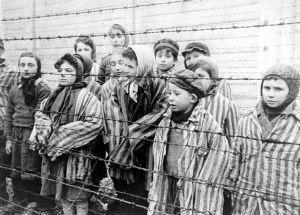Auschwitzista vapautettuja lapsia piikkilangan takana.