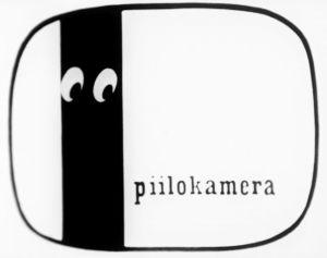 Piilokamera-ohjelman tunnusgrafiikka (sijoitettu mustalle taustalle)