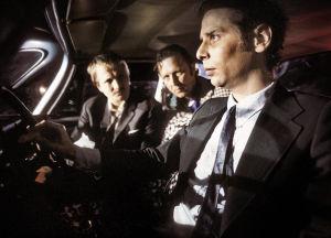 Kolme miestä auton etupenkillä Katsastus-elokuvassa.