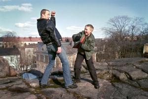 Mies ja poika nyrkkeilevät kalliolla.