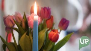 Kuvassa kynttilä ja kukkia.