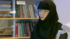Nunna Kristoduli haastateltavana kirjahyllyn edessä