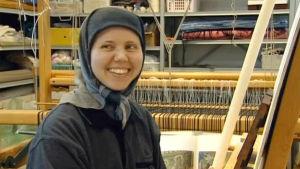 Sisar Juliaana hymyilee leveästi maalaustelineen edessä