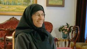 Sisar Leena hymyilee haastattelussa. Taustalla taulu ja tuoleja