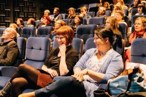 Yleisöä. Etualalla olevet naiset nauravat.