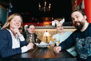 Ravintolapöydässä neljän hengen seurue skumppalasit käsissä hymyilevät.