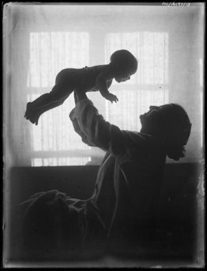 Mor lyfter barn i luften.