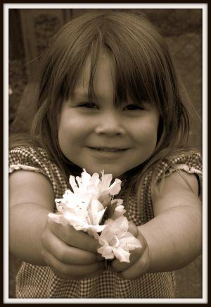 Flicka med blommor i handen.