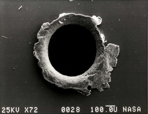 Hål i satellit efter en träff av en mikrometeorit.