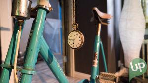 Kuvassa kello ja kuntopyörä.
