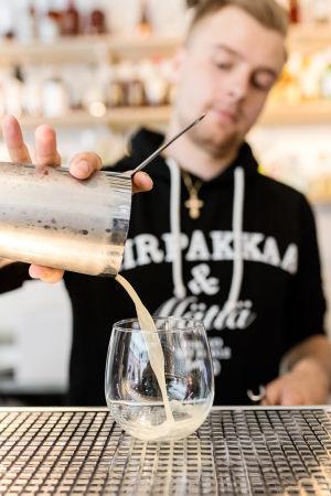 Bar manager Andreas Cederström kaataa drinkkiä shakerista lasiin.