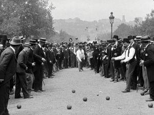 Miehet pelaavat kuulapeliä puistossa.
