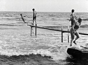 Uimarit hyppivät laiturilta mereen.