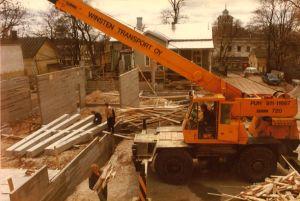 Lyftkran och byggarbetare på en byggarbetsplats.